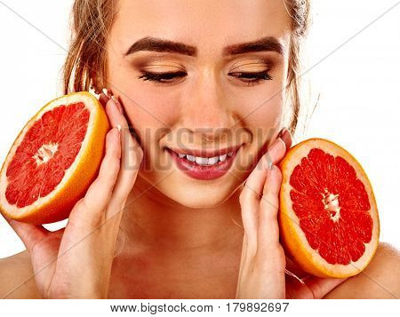Facial mask from fresh fruits for woman . Girl with beautiful face holds halves of grapefruit for homemade organic skin and hair therapy. Concept of healthy food and beauty diet.