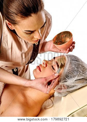 Mud facial mask of woman in spa salon. Massage with clay full face. Girl on with therapy room. Female lying wooden spa bed. Beautician with bowl therapeutic procedure isolated background.