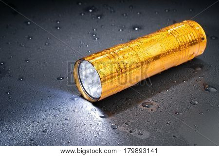 Pocket Led Flashlight In The Rain On A Dark Surface. Water Drops.