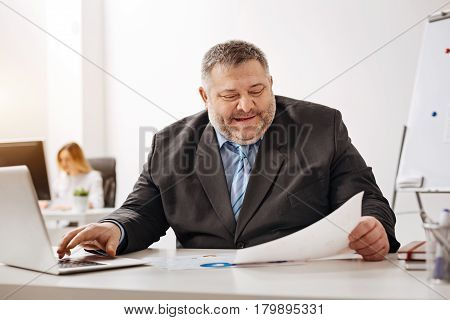 Excellent rates. Joyful cute chubby man feeling satisfied with the results while reading a recent sales report and using his laptop