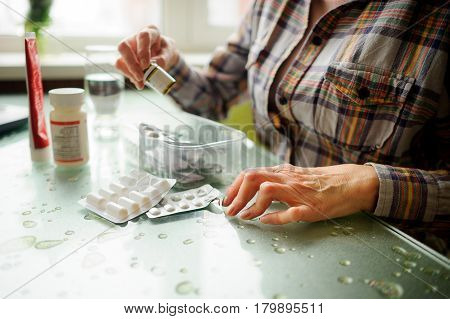 The woman having rheumatoid arthritis takes medicine. Hands are deformed.