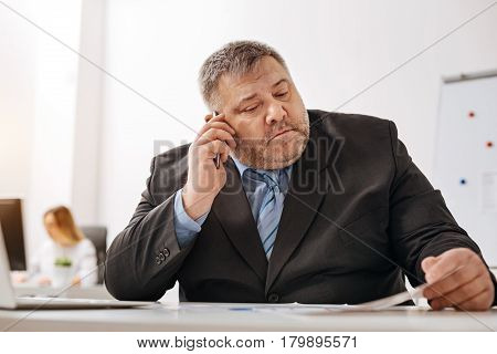 Make it clear to me. Focused involved chubby man calling his colleague from another department while examining recent sales report and seeing some mistakes