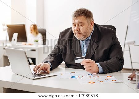 Keeping a record. Focused attentive concerned man checking his bank account while using an online service and entering digits from his card