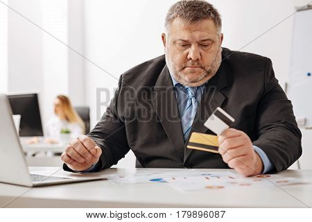 I should have some savings. Worried upset chubby guy feeling sad and looking at his credit card after checking his bank account online