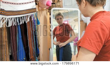 A customer is trying on a blue waistband. The waistband is available in one standard size. Easy to wear accessory that can be worn by any age or size.