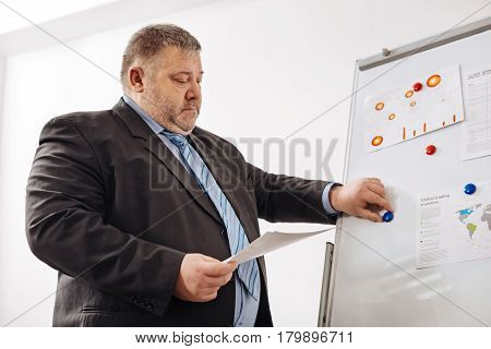 Illustrating the numbers. Diligent attentive well trained specialist using a pin board for arranging some schemes demonstrating data from the resent report