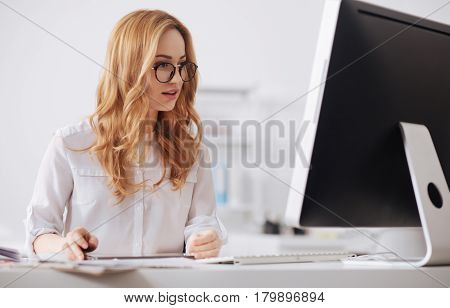 Enjoying my job. Involved happy young businesswoman sitting at the table in the office and working while using tablet and reading documents