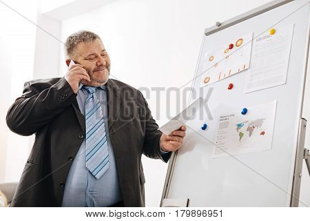 We have a deal. Delighted persistent chubby man reaching an agreement with his business partner while telling him about positive results during the phone call