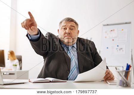 Now go work. Ambitious tireless overweight worker sitting at the desk and managing the working process while holding a decree from his boss in his hand