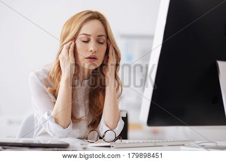 Suffering from ache. Prostrate exhausted young office manager sitting at the table in the business center and working while touching her head and feeling tired