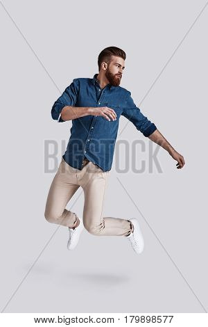 Feeling comfortable in his style. Full length of handsome young man looking away while jumping against grey background