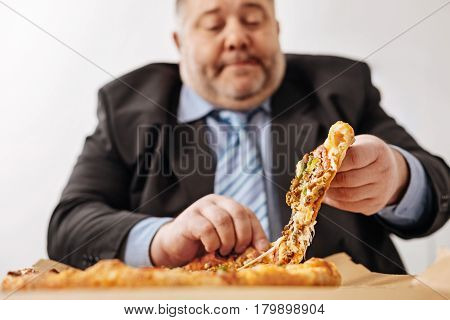 Delicious and unhealthy. Overweight middle aged mediocre employee loving junk food and ordering a pizza in office every time he having a lunch
