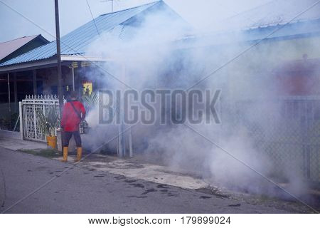 low light, evening when the mosquito most active time,worker fogging residential area with insecticides to kill aedes mosquito breeding ground, carrier of dengue virus