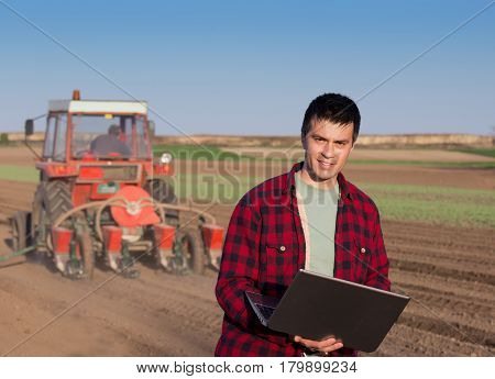 Farmer With Laptop And Tractor Sowing