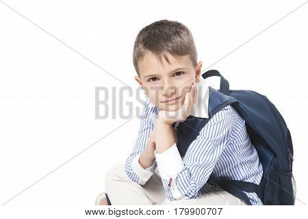 Young cool caucasian boy with school bag sits