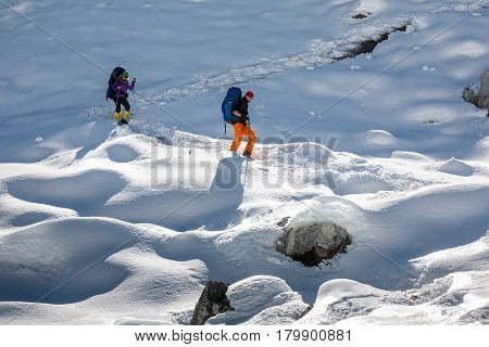 Trekkers are crossing Gokyo glacier in Khumbu valley on a way to Everest Base camp