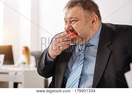 Threatening your own health. Hilarious weak willed corpulent man having a lunch break and stuffing himself with doughnuts while sitting at his workplace