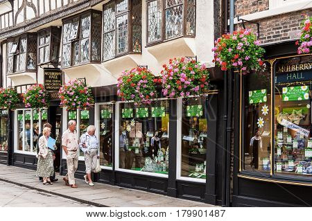 York North Yorkshire United Kingdom - June 23 2006: Elderly tourists walking along the old street and looking through the store window in York.