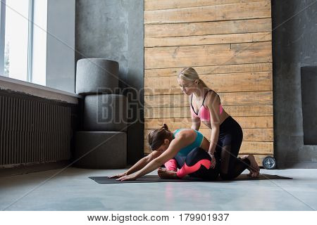 Yoga class instructor helps beginner to make asana exercises. Teacher assists to make cobbler pose, baddha konasana. Healthy lifestyle in fitness club. Stretching with coach
