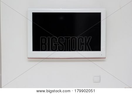 Wide screen TV on the white wall