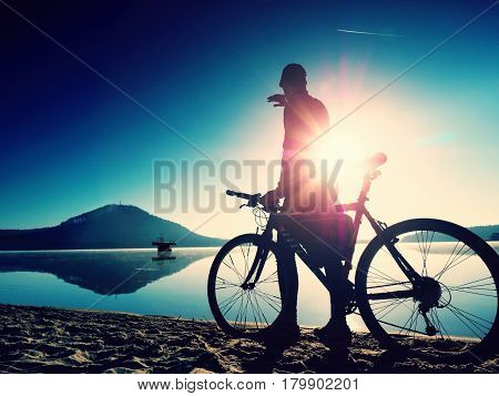 Silhouette Of Sportsman  Holding Bicycle On Lake Beach, Colorful  Sunset Cloudy Sky In Background