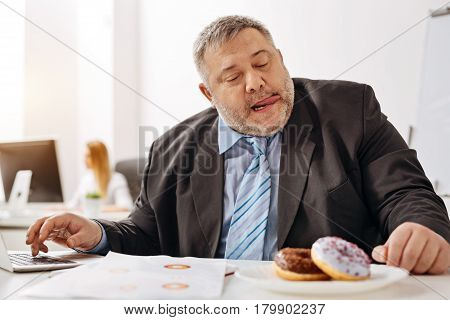 Watering mouth. Immoderate compulsive witty guy feeling strong desire of taking a bite of a doughnut lying on his desk