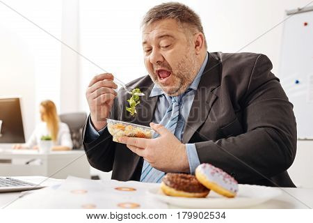 Imagining tastier things. Stout unhealthy office worker eating a salad trying being healthy but still wanting eating some junk food
