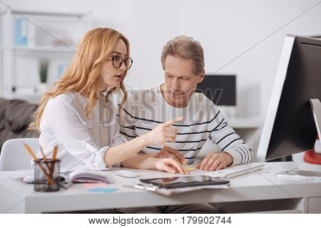 Affair in the office. Unmannered flirting aging businessman sitting in the office and working on the project while flirting and staring at young colleague