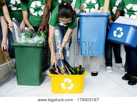 People in group helping together to put up bottles for recycle