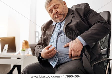 Daily routine. Middle aged unhealthy chubby man holding a syringe with his medicine and preparing himself for injecting it