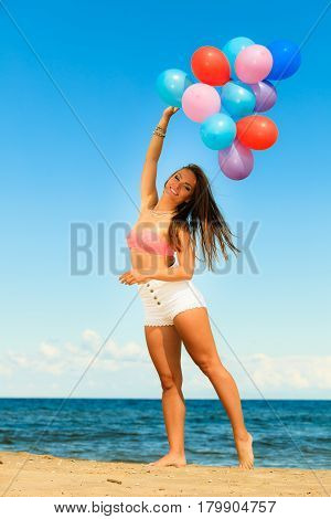 Summer holidays celebration and lifestyle concept - attractive athletic woman teen girl with colorful balloons outside on beach seashore background
