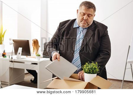 Taking my things with me. Devastated emotional chubby employee collecting all his things in a box while preparing leaving his workplace