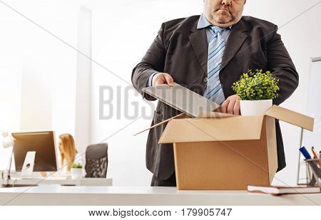 Leaving nothing behind. Overweight unproductive office worker being a victim of personnel reduction and gathering his stuff before leaving the office