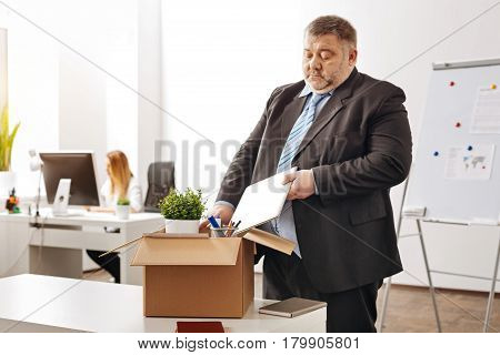 All my belongings. Sad irritated chubby worker being fired and standing by his table having his things packed in a large box