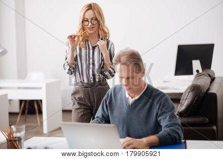 You do not even expect . Aphrodisiac young active secretary standing in the office behind the colleague while expressing passionate emotions and seducing the man