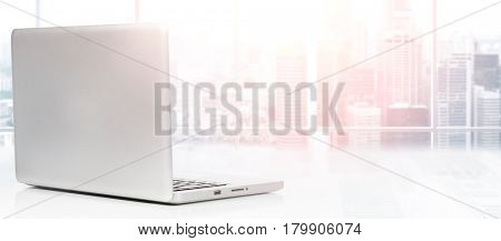 Laptop on table in office with panoramic view of modern downtown skyscrapers at business district