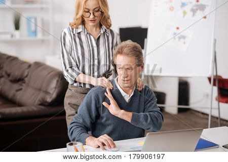 Hate inappropriate behavior. Involved puzzled mature man sitting in the office and demonstrating negative emotions while working and expressing indignation towards colleagues seduction