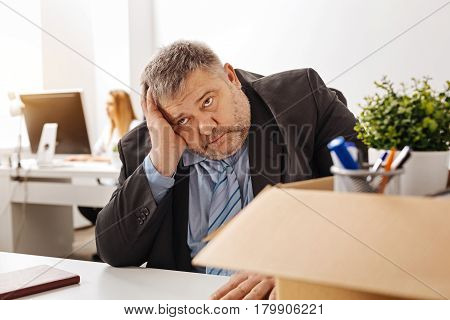 Awful situation. Overwhelmed sorrowful pudgy man sitting at his desk and thinking about what he doing wrong in his work