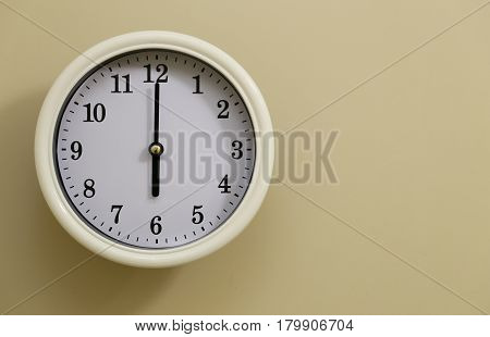 The time of the white wall clock is 6 o'clock