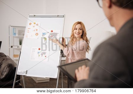 My enjoyable working routine. Creative shy skilled office manager standing near the white board in the office and pointing on it while representing the project in front of the boss