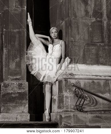 Artistic look. Monochrome portrait of a beautiful ballet dancer posing near the wall looking away thoughtfully soft focus picture