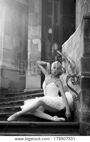 Alone in here. Portrait of a beautiful young female ballet dancer sitting on stairs touching her face gracefully monochrome shot