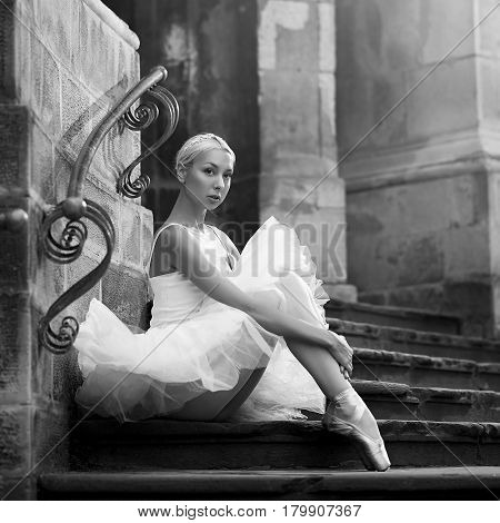 So untouched and innocent. Monochrome portrait of a beautiful ballerina wearing white sitting on the stairs of an old castle