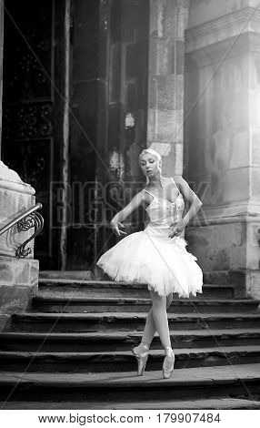 Dancing is her passion. Stunning ballerina dancer posing outdoors near an old castle monochrome soft focus