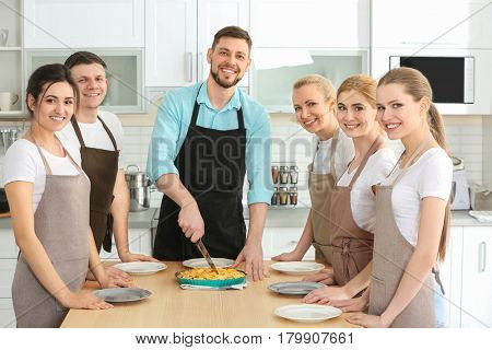 Male chef and group of people with tasty pie at cooking classes