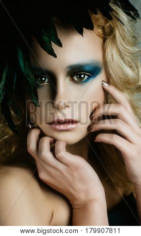 Beautifull girl in image of a bird, color fashion make up with feathers
