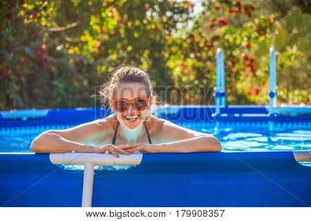 Happy Healthy Woman In Swimming Pool In Sunglasses