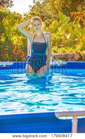 Healthy Woman Standing In Blue Swimsuit In Swimming Pool