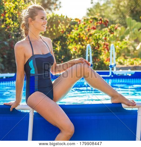 Smiling Woman Sitting On Swimming Pool And Looking Into Distance