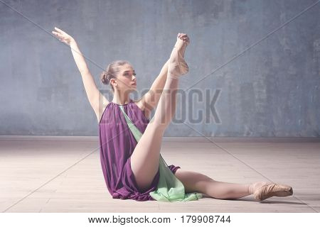 Young beautiful ballerina dancing in studio